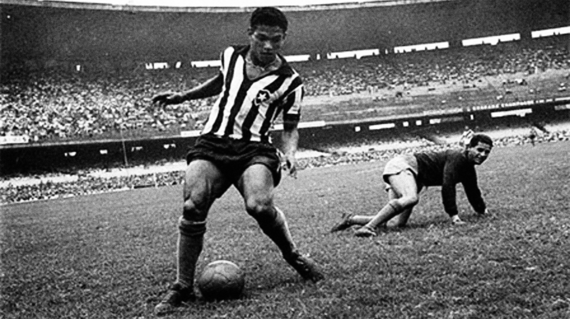 A black and white photo of a soccer (football) player with the ball near his feet, running. His legs are bowed.