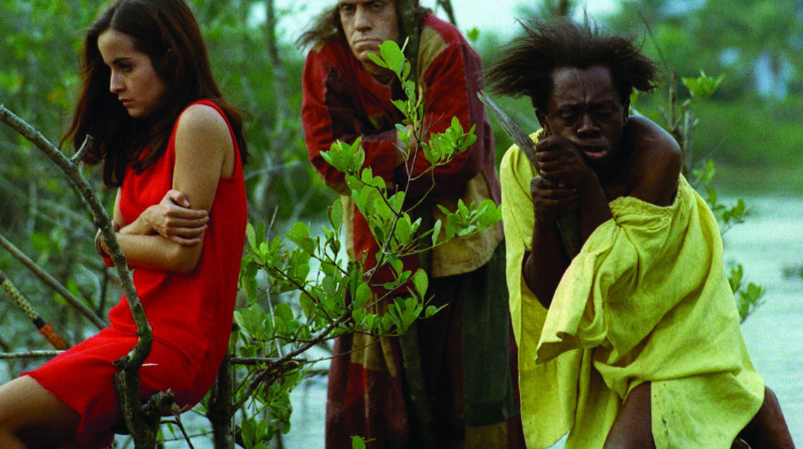 Three figures are huddled in the jungle with a river behind them. On the left, a light skinned woman with a red dress holds her arms across her chest and sits on the branch of a low shrub. Behind, a tall light skinned man holds a similar clothes. He is wearing a long, patchwork robe. On the right, a dark skinned man is leaning on a stick. He is wearing an ill-fitting chartreuse garment. His eyes are downcast, all look troubled.
